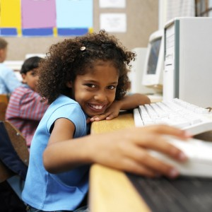 Young Girl at School Holding a Computer Mouse